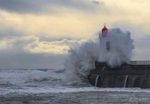 Photo du phare rouge submergé par vague de la tempête