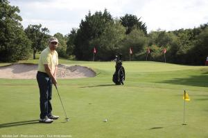 Photo golfer avec putter sur practice