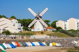 Photo de barques multicolores avec le moulin de jard sur mer en fond