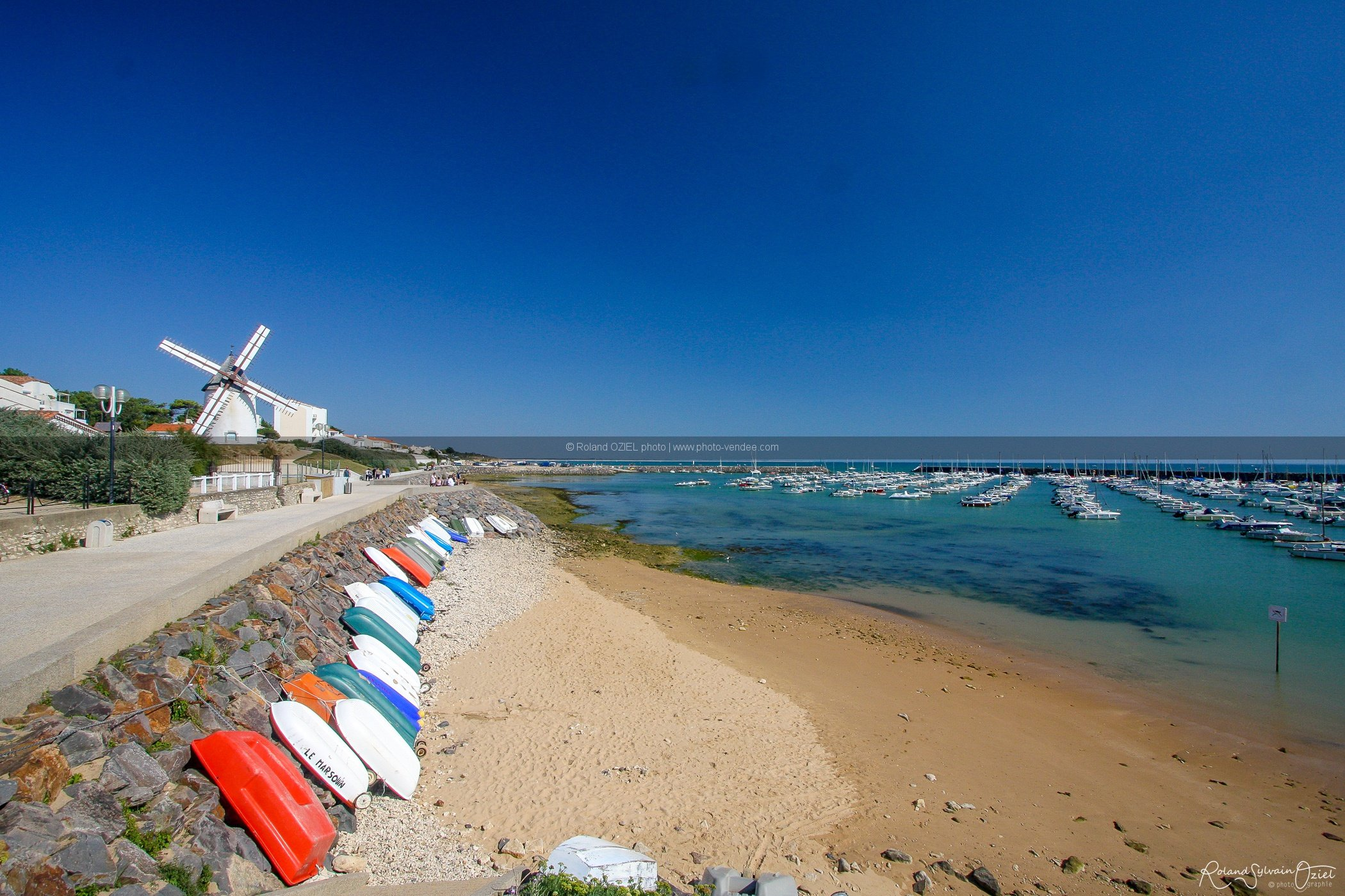 Photo du moulin de jard sur mer avec barques multicolores en premier plan